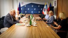 Grupa osób siedzi przy długim stole na sali konferencyjnej w urzędzie marszałkowskim