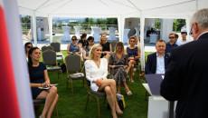 Uczestnicy Spotkania siedząc na krzesłach pod białym namiotem przeciwsłonecznym, wsłuchują się w głos Marszałka Andrzeja Bętkowskiego