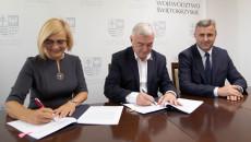 Trzy osoby siedzą przy stole. Umowę podpisują Wicemarszałek Renata Janik, Marszałek Andrzej Bętkowski. Za nimi ścianka promocyjna z herbem województwa świętokrzyskiego