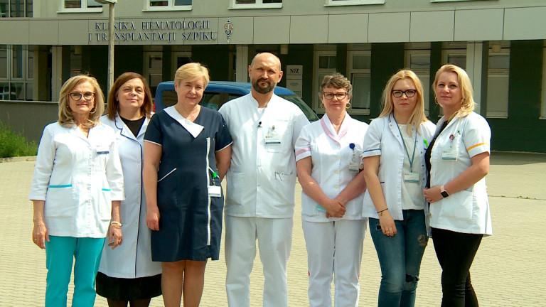 Zespół Do spraw Żywienia Klinicznego Świętokrzyskiego Centrum Onkologii. Kobiety w fartuchach medycznych stoją przed wejściem do szpitala, pomiędzy kobietami stoi jeden mężczyzna