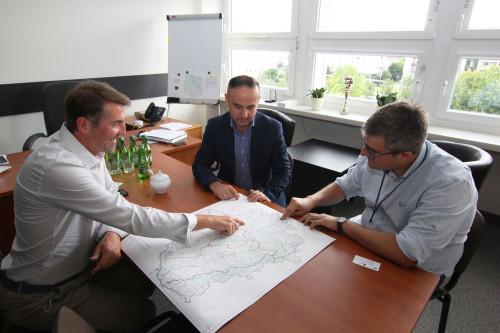 Wskazując miejsca na mapie trzech mężczyzn dyskutuje na temat przebiegu tras rowerowych