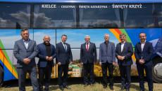 Grupa mężczyzn stoi z boku kolorowego autobusu. Kielce, Cedzyna, Święta Katarzyna, Święty Krzyż