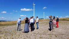 Farma Wiatrowa. Grupa osób stojąc w polu patrzy w górę. Obok nich bardzo duże wiatraki