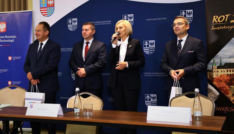 Cztery osoby stoją przed ścianką promującą województwo świętokrzyskie. Od lewej Andrzej Gut-Mostowy, Marcin Piętak, Renata Janik i Marcin Różycki