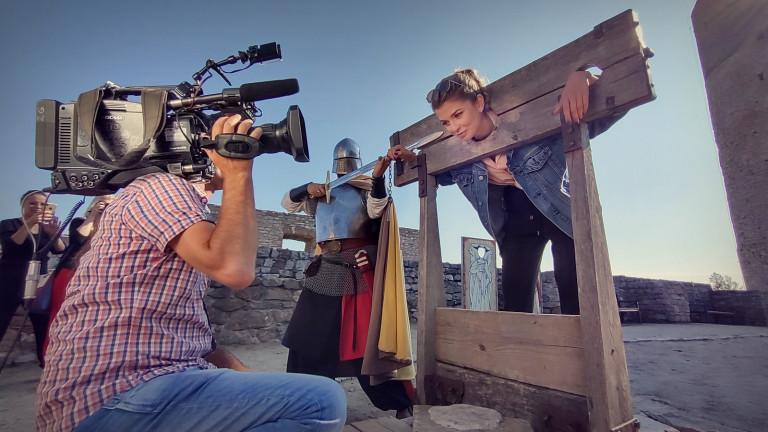 Mężczyzna z kamerą nagrywa kobietę zamkniętą w dybach. Obok stoi rycerz w historycznym kostiumie z długim mieczem. Tereny Zamku w Chęcinach
