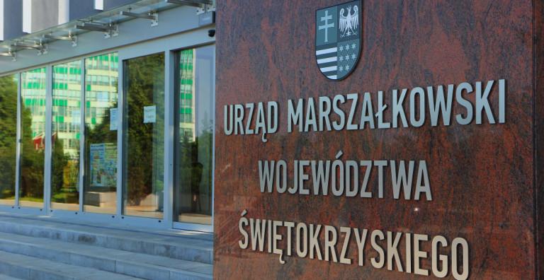 Kamienna tablica stojąca przed wejściem do budynku Urzędu Marszałkowskiego z napisem Urząd Marszałkowski Województwa Świętokrzyskiego