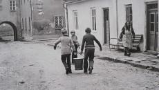 chłopcy niosący wiadro z wodą na starej piaszczystej ulicy biało-czarne zdjęcie