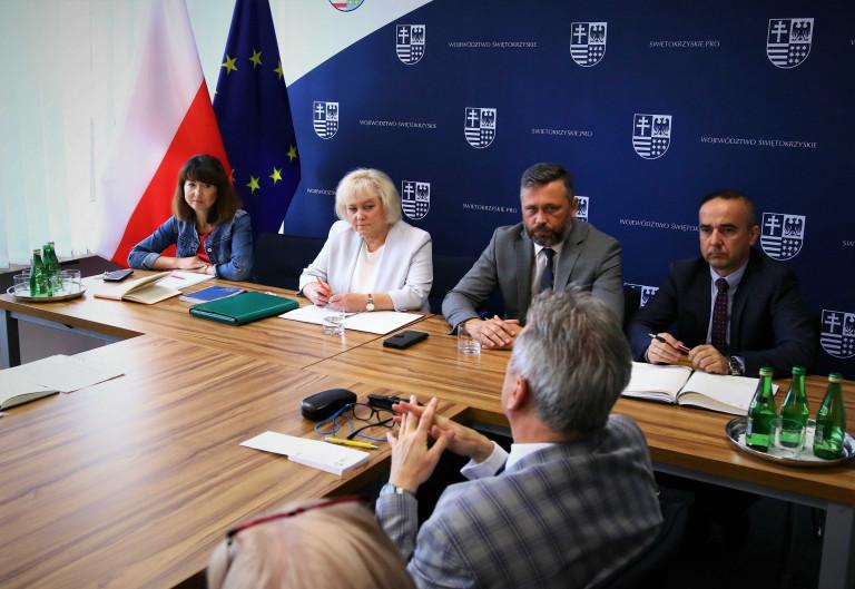 Członek Zarządu Województwa Świętokrzyskiego Tomasz Jamka siedzi wśród uczestników spotkania
