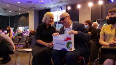 Wicemarszałek województwa świętokrzyskiego Renata Janik siedzi obok niewidomego mężczyzny; rozmawiają